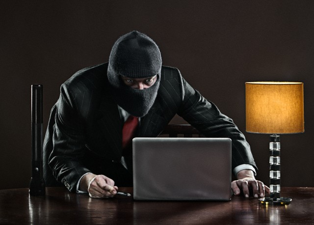 Man wearing balaclava inserting memory stick to laptop on desk
