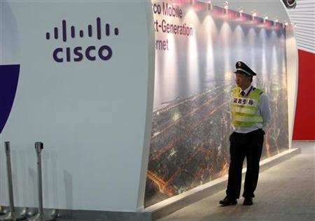 A security guard walks past a Cisco display at the Mobile Asia Expo in Shanghai
