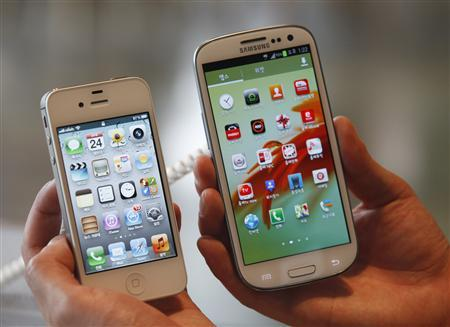 File photo of an employee holding Apple's iPhone 4s and Samsung's Galaxy S III at a store in Seoul